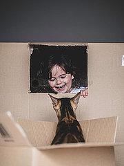 Maedchen und Katze spielen im Pappkarton p1522m2072809