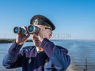 Kapitaen eines Schiffes auf einem Fluss schaut durch ein Fernglas p390m2076231