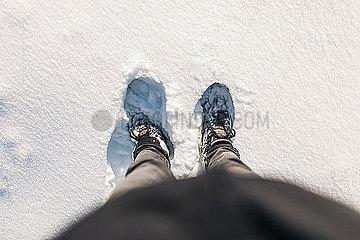 Mann steht mit Schuhen in Neuschnee bei Sonnenschein p1497m2071426