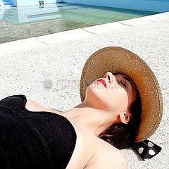 Junge Frau mit Sommerhut beim Sonnenbaden p1521m2081642