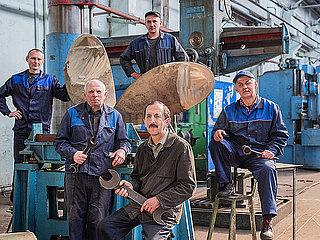 Mitarbeiter einer Schiffsfabrik posieren vor einer Schiffsschraube p390m2076205