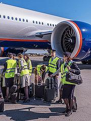 Flugzeugcrew mit Second Officer und Stewardessen beim Boarding in ein Flugzeug