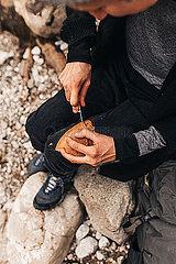 Frau schneidet Brot mit Messer in der Natur auf Wanderung