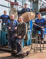 Mitarbeiter einer Schiffsfabrik posieren vor einer Schiffsschraube