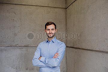 Freundlicher junger Mann vor einer Betonwand