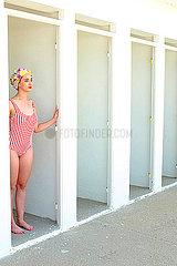 Junge Frau mit Badekappe in einer Umkleide
