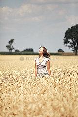 Maedchen sonnt sich in einem Kornfeld