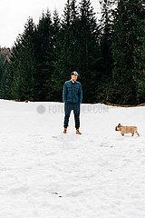 Mann geht mit HUnd im Schnee spazieren