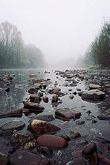 Stony river bank in fog