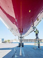 Flugzeug Boeing 777-300 wird vom Bodenpersonal auf dem Flughafen gewaretet und ueberprueft