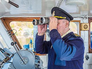 Kapitaen eines Schiffes auf einem Fluss schaut durch ein Fernglas