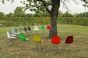 Stuhlreihe um einen Baum