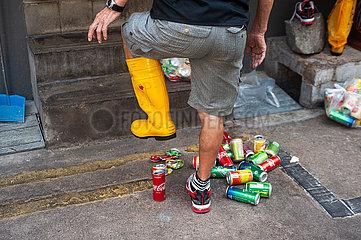 Singapur  Republik Singapur  Mann mit Gummistiefel zertritt leere Getraenkedosen