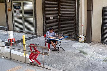 Singapur  Republik Singapur  Mann sitzt in Chinatown mit Laptop am Schreibtisch