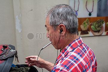Singapur  Republik Singapur  Mann hoert in Chinatown Musik mit Kopfhoerern
