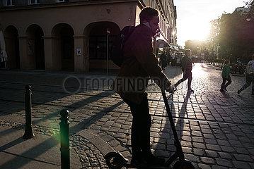 Polen  Wroclaw - Junger Mann auf einem e-scooter mit handy am Ohr