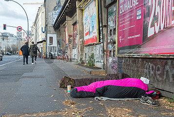 Zwei Wohnungslose campieren auf einer Strasse.