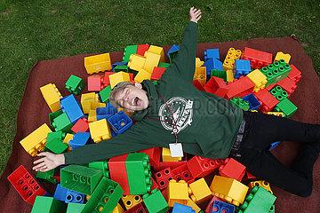 Hannover  Deutschland  Junge liegt lachend auf ueberdimensionalen Legosteinen