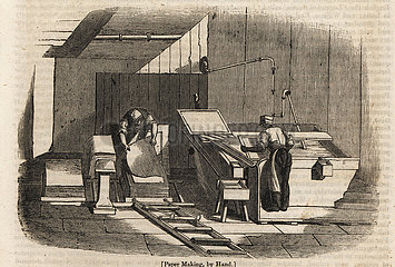 Workers making sheets of paper by hand.