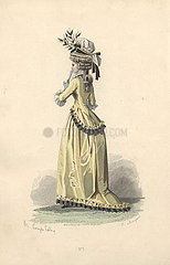 Woman in wig  bonnet trimmed with foliage  yellow silk jacket and matching long skirt.