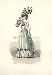 Woman in extravagant tall floral bonnet  wearing a flower-trimmed pale green dress  holding a fan.