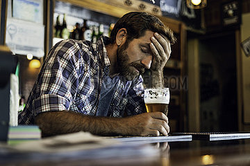 Sad man sitting in beer bar