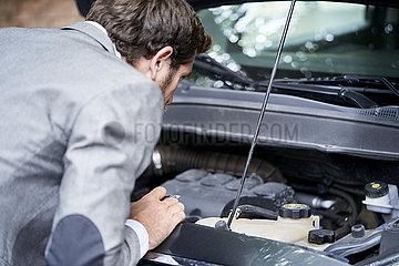 Man examining car engine
