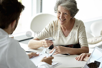 Senior woman talking with doctor in clinic