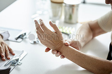 Senior woman showing her hand to doctor