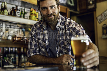 Man holding beer glass at counter