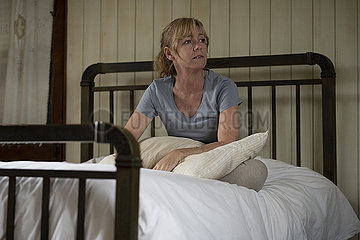 Thoughtful woman sitting on bed