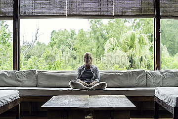 Mature woman sitting on sofa