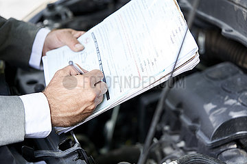 Man's hand writing on documents