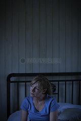 Thoughtful sad woman sitting on bed