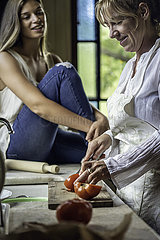 Mother and daughter preparing food in kitchen