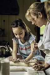 Granddaughter and grandmother preparing food