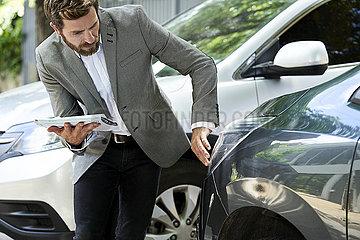 Salesman examining car