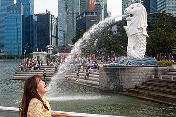 Singapur  Republik Singapur  Tourist posiert fuer Foto im Merlion Park in Marina Bay