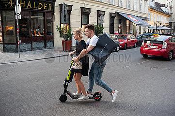 Wien  Oesterreich  Junges Paar faehrt Elektroroller des Anbieters Hive