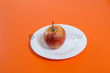 Ein Apfel liegt auf einem Teller