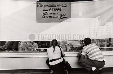 DEU  Deutschland  30. Juni 1990  Berlin  der letzte Tag vor der Einf?hrung der D- Mark in der DDR  Passanten versuchen die neuen Auslagen zu betrachten 30. Juni 1990  Berlin  vor der Waehrungsunion