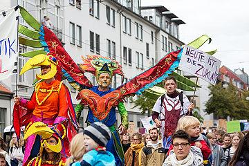 Deutschland  Bremen - fridays for future - Demonstration  erwachsene als Paradiesvoegel verkleidete Teilnehmer auf Stelzen