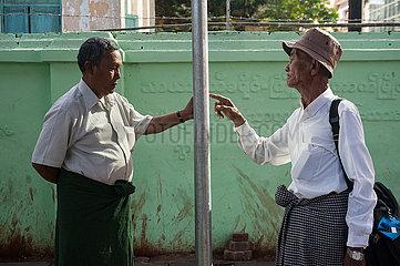 Yangon  Myanmar  Maenner studieren die Fahrplaene an einer Bushaltestelle