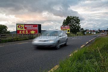 Irland  Dundalk - Werbung fuer Wechselstube direkt auf der irischen Grenze an einer Landtrasse Richtung Belfast (nach rechts)