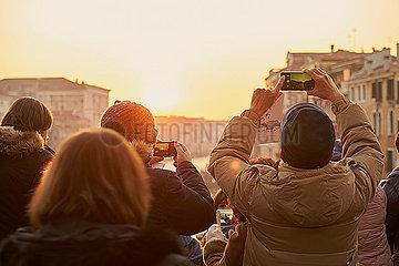 Menschen fotografieren mit Smartphone den Sonnenuntergang  Venedig