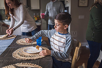 Elementary age boy eating pancakes for breakfast