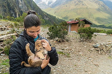 Young Hip Woman Hugging A Puppy While Exploring The Andes Mountains.
