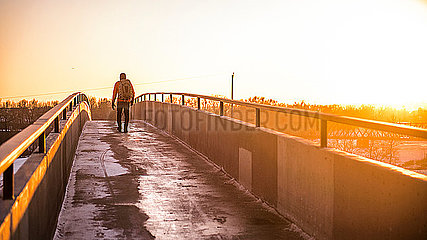 Man walking toward the sun at sunset on footbridge with backpack