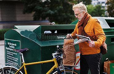 Man putting garbage into recycling bin