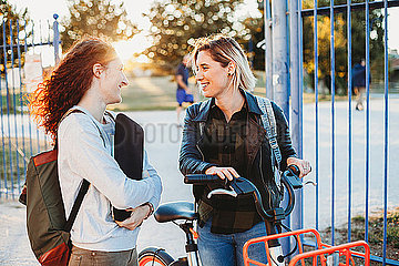 Two young student talking at the park together
